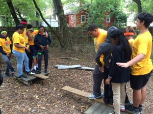 Advance College Academy students working on a strategy to get everyone on the same platform without touching the ground during their team building visit to Richmond Ropes.